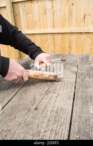 male hands using knife to carve into branch. - Stock Photo