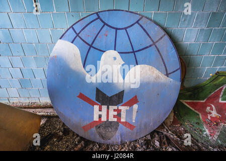 Old Soviet peace sign with 'no' word on a bomb in abandoned Jupiter Factory in Pripyat city of Chernobyl Zone of - Stock Photo