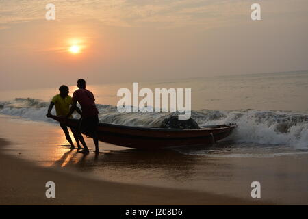 Men returning from fishing early in the morning with their boat - Stock Photo