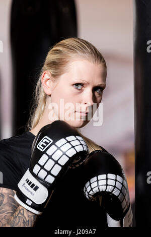 Young woman, tattooed, boxing at a sandsack in a boxing studio, Bavaria, Germany - Stock Photo