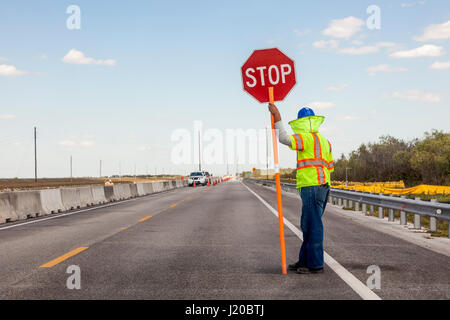 Road construction on the highway, Worker holds a stop sign to control the traffic - Stock Photo