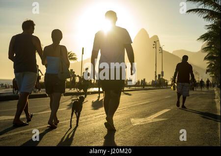 RIO DE JANEIRO - FEBRUARY 12, 2017: Brazilians enjoy a sunset afternoon on the car-free beachfront street in Ipanema. - Stock Photo