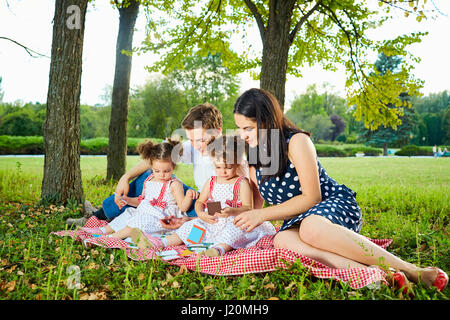 Happy family in the park summer, autumn. Parents and two daughters sitting, playing . - Stock Photo