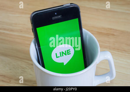 Bangkok, Thailand - April 22, 2017 : Apple iPhone5s in a mug showing its screen with LINE messaging mobile application - Stock Photo