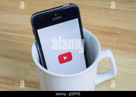Bangkok, Thailand - April 22, 2017 : Apple iPhone5s in a mug showing its screen with Youtube logo. - Stock Photo
