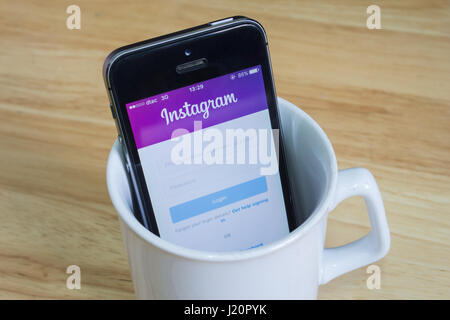 Bangkok, Thailand - April 22, 2017 : Apple iPhone5s in a mug showing its screen with Instagram logo. - Stock Photo