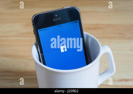 Bangkok, Thailand - April 22, 2017 : Apple iPhone5s in a mug showing its screen with Facebook logo. - Stock Photo
