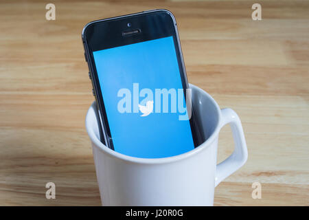 Bangkok, Thailand - April 22, 2017 : Apple iPhone5s in a mug showing its screen with Twitter logo. - Stock Photo