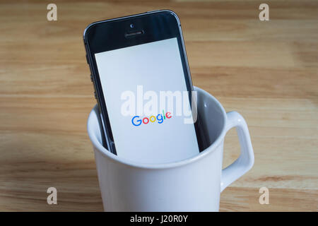 Bangkok, Thailand - April 22, 2017 : Apple iPhone5s in a mug showing its screen with Google logo. - Stock Photo