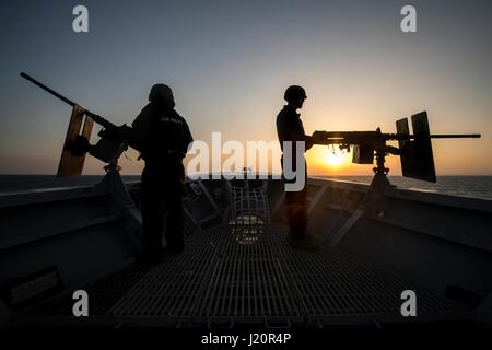 U.S. Navy sailors are silhouetted by the setting sun as they man .50 caliber machine guns aboard on the bow of the - Stock Photo