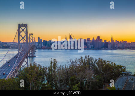 Classic panoramic view of famous Oakland Bay Bridge with the skyline of San Francisco illuminated in beautiful twilight - Stock Photo