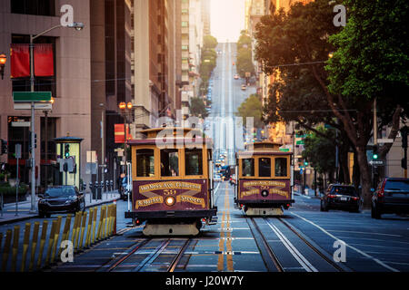 Classic view of historic traditional Cable Cars riding on famous California Street in beautiful early morning light - Stock Photo