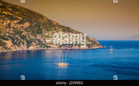 Panorama view of sailing yachts on the Mediterranean Sea at famous Amalfi Coast in beautiful golden evening light - Stock Photo