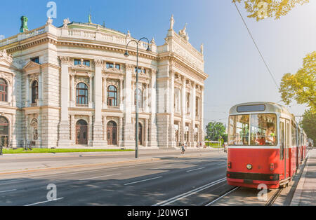 Classic view of famous Wiener Ringstrasse with historic Burgtheater and traditional red electric tram on a beautiful - Stock Photo