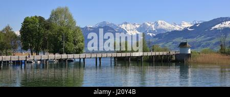 Timber gangplank in Rapperswil. Lake Zurichsee and snow capped mountains. Spring scene in Switzerland. - Stock Photo