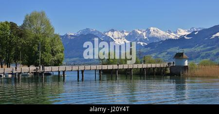 Springtime in Rapperswil. Gangplank on lake Zurichsee. Green trees and snow capped mountains. - Stock Photo