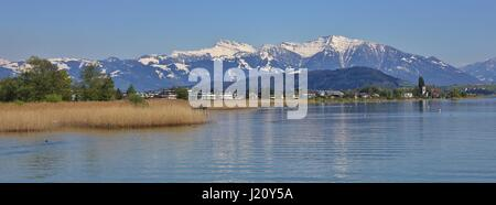 Shore of lake Zurichsee and snow capped mountain Grosser Speer. View from Rapperswil. - Stock Photo