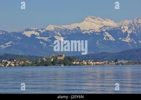 Spring scene at lake Zurichsee. Medieval castle in Rapperswil. Grosser Speer, snow capped mountain. - Stock Photo