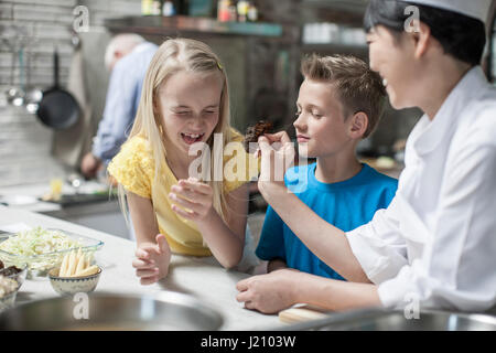 Female chef with girl pulling faces in cooking class - Stock Photo
