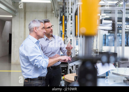 Two businessmen in modern factory hall talking at computer monitor - Stock Photo