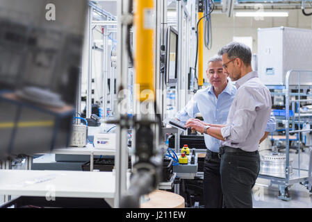Two businessmen in modern factory hall using computer - Stock Photo
