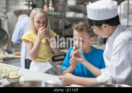 Boy and girl smelling food from female chef in cooking class - Stock Photo