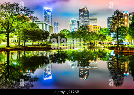 Charlotte, NC skyline reflected in Marshall Park pond on a foggy night - Stock Photo