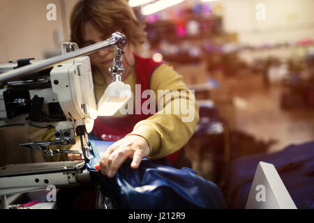 Woman working in sewing industry on machine - Stock Photo