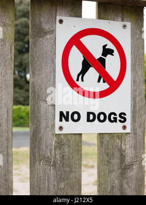 a sign saying no dogs red black and white park safety clean area private icon circle crossed on fence near playground - Stock Photo