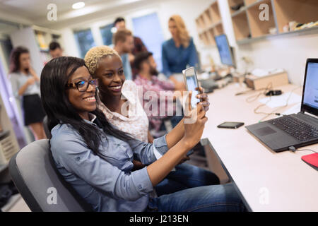 Beautiful female coworkers working at company taking selfie - Stock Photo
