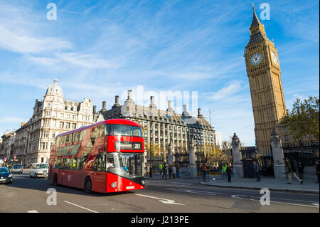LONDON - NOVEMBER 16, 2016: Red double-decker bus passes the entrance to Westminster Palace and the Houses of Parliament. - Stock Photo