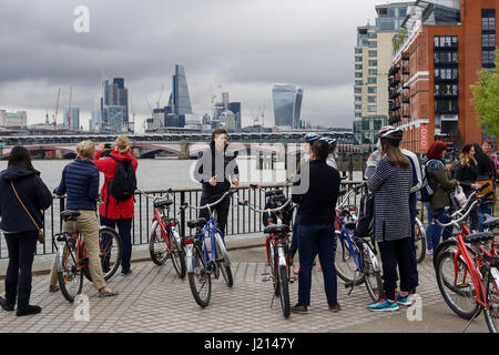 Tourists on a cycling tour along the south bank of the River Thames in London - Stock Photo