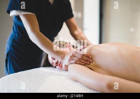 Masseur treating masseuse at spa wellness saloon - Stock Photo