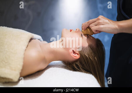 Rejuvenating relaxing massage by masseur at massage saloon - Stock Photo