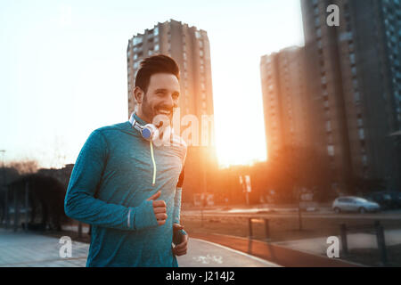 Handsome runner exercising by running and jogging  in city - Stock Photo