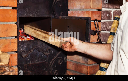 Man puts firewood in a stove, close-up of a hand. - Stock Photo