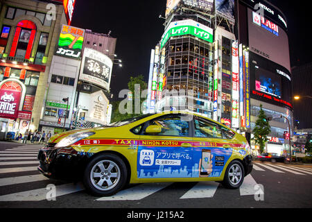 Tokyo, Japan - 19 June 2016: Toyota Prius, energy efficient taxicab in Shinjuku, Tokyo. Night scene  on busy intersection - Stock Photo