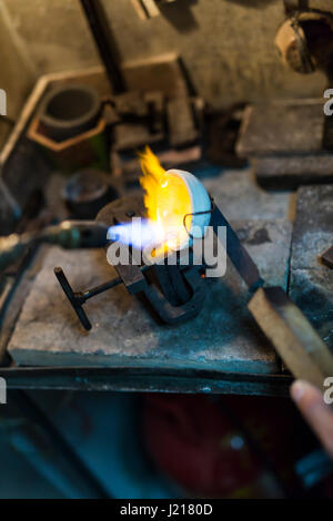 Jeweler welding gold the traditional way - Stock Photo