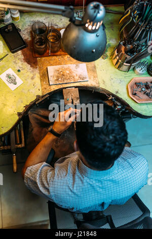 Craftsman working on workbench surrounded by his tools - Stock Photo