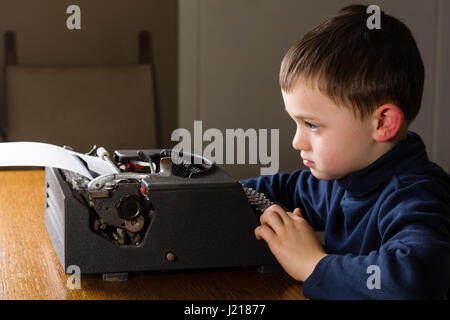 Cute little boy typing a letter on a vintage black typewriter at home. Looking concentrated, bored or in a bad mood - Stock Photo