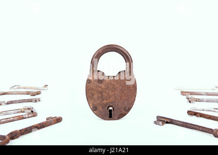 Ancient rusty padlock with collection of keys isolated on white background. Set - Stock Photo
