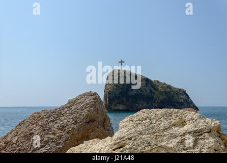 Scenic view towards St. Appearance Rock or Holy Cross Rock from stones at Jasper beach near famous St. George Monastery - Stock Photo