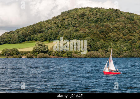 ULLSWATER, UNITED KINGDOM - AUGUST 18, 2012: Three unidentified people are sailing on Ullswater in the English Lake - Stock Photo