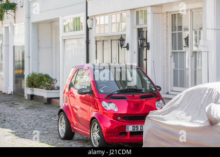 bright red electric smart car parked on a London street, London, England, UK - Stock Photo
