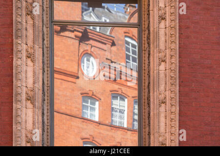reflection of an old brick building in London in an a window with elaborate molding, London England, UK - Stock Photo