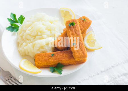 Fried fish fingers, mashed potatoes and lemon. Delicious lunch with fish sticks and vegetables, convenient seafood - Stock Photo