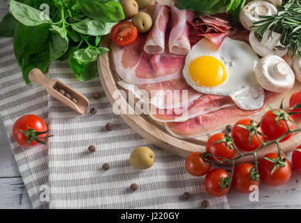 Healthy Mediterranean breakfast groceries: fried eggs, ham, vine tomatoes, mushrooms, basil, olives, rosemary on - Stock Photo