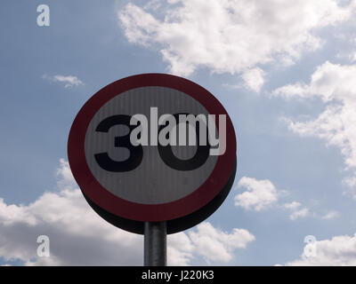 a road traffic sign with a sky background saying 30 speed limit near school accident crash cars fast and slow warning - Stock Photo