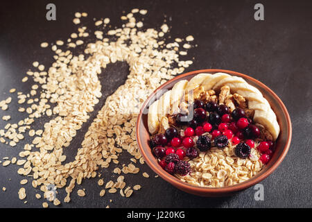 Oatmeal in brown clay bowl with berries (blackcurrants, redcurrants, blackberries), bananas and walnuts ready to - Stock Photo