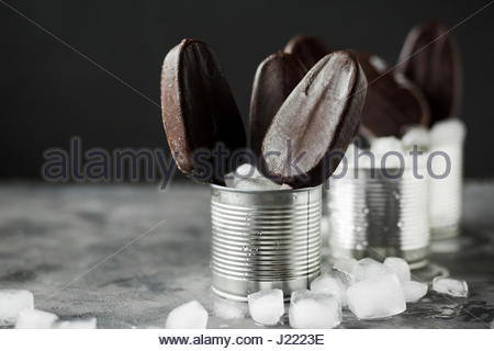 Chocolate ice cream on a stick in an iron jar on a black background. Chocolate dessert. Ice - Stock Photo